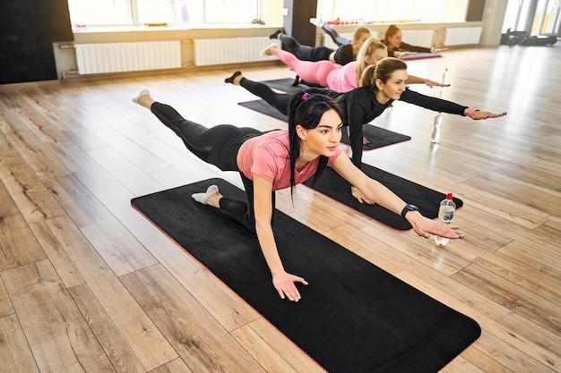 Groupe de femmes sportives faisant des pompes sur le sol et des exercices d'étirement dans la salle de gym