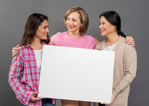 Groupe de femmes tenant une feuille de papier vierge