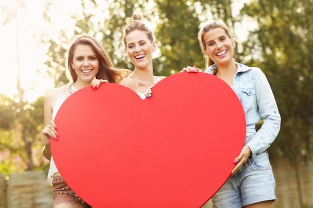 Groupe de femmes tenant un grand coeur à l'extérieur