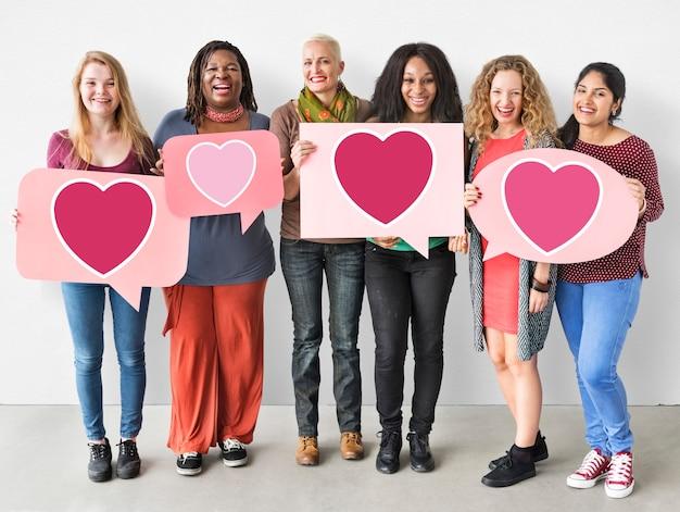 Groupe de femmes tenant des icônes de coeur