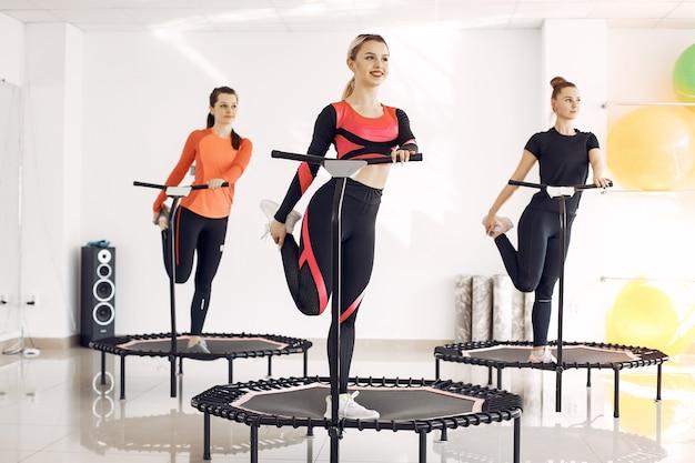 Groupe de femmes sur trampoline sportif. entraînement de remise en forme.