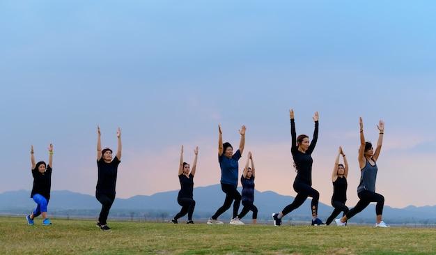 Groupe femmes yoga au coucher du soleil sur le lac