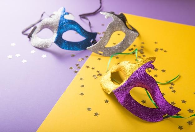 Un groupe festif et coloré de mardi gras ou masque carnivale sur fond jaune violet. masques vénitiens.