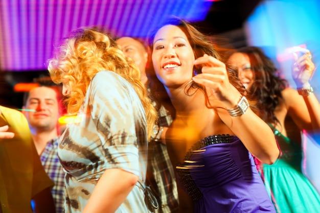 Groupe de fêtards - hommes et femmes - dansant dans un disco à la musique