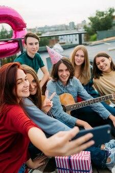 Groupe de fête d'anniversaire selfie sur un toit. dépendance moderne au partage dans les réseaux sociaux. mode de vie des jeunes bff