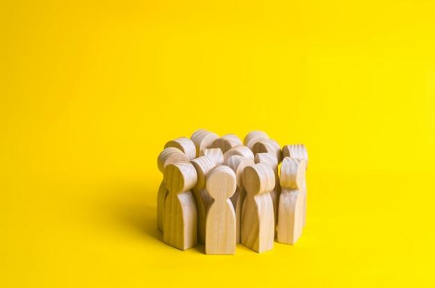 Groupe de figurines de gens en bois sur fond jaune. foule, réunion, activité sociale.