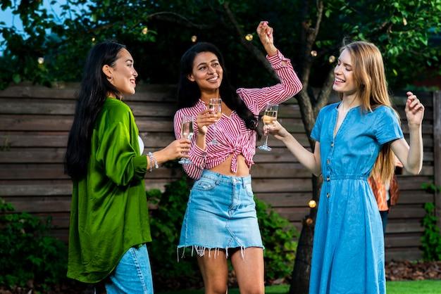Groupe de filles dansant ensemble avec des boissons