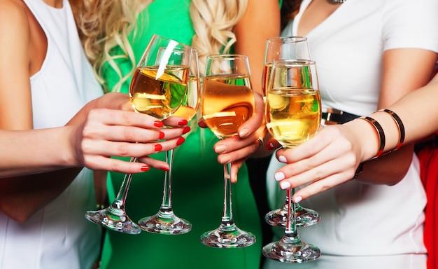 Groupe de filles faisant la fête tinter les flûtes avec du vin mousseux