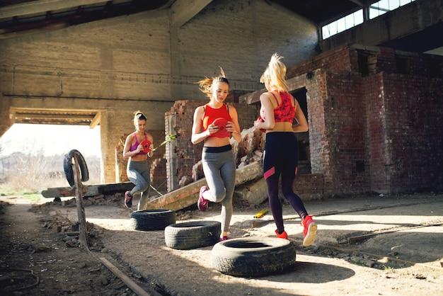 Groupe de filles de forme traverse des pneus avec des haltères dans les mains.