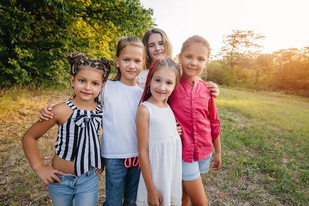 Un groupe de filles gaies sourient et jouent dans le parc pendant le coucher du soleil. camp d'été pour enfants.