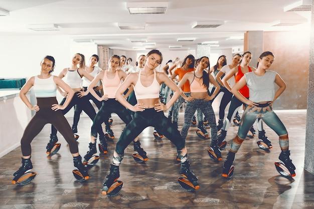 Groupe de filles avec des habitudes saines faisant des exercices dans des chaussures de sauts kangoo. intérieur du gymnase. contrôlez l'esprit, contrôlez le corps.