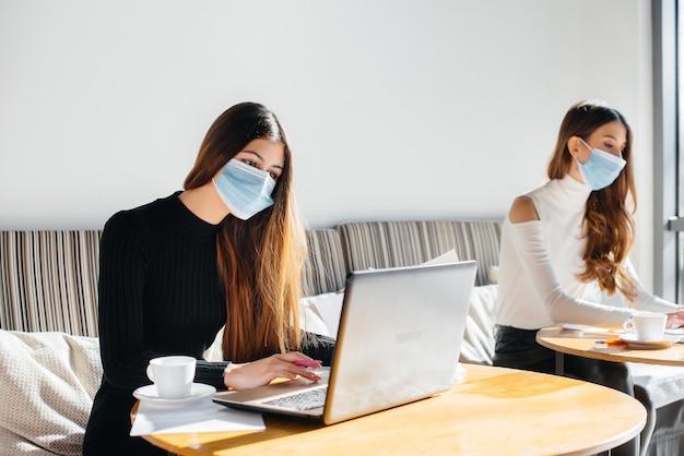 Un groupe de filles masquées garde une distance sociale dans un café lorsqu'elles travaillent sur des ordinateurs portables.