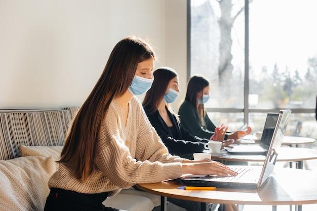Un groupe de filles masquées gardent une distance sociale dans un café lorsqu'elles travaillent sur des ordinateurs portables.