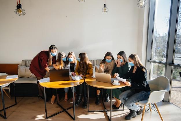 Un groupe de filles masquées s'assied dans un café et travaille sur des ordinateurs portables. enseigner aux étudiants.