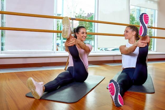 Un groupe de fitness fait des exercices pour étirer les muscles lors d'une leçon de fitness.