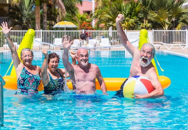 Groupe fou de personnes âgées jouant au volley-ball dans la piscine avec filet gonflable et ballon
