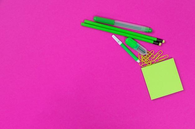 Un groupe de fournitures de bureau vert vif se trouve dans le coin supérieur droit sur rose isolé