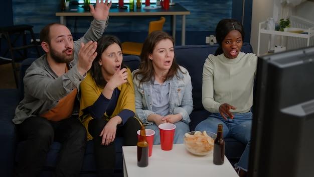 Groupe frustré de personnes multiethniques traînant ensemble tard dans la nuit dans le salon en regardant la télé...