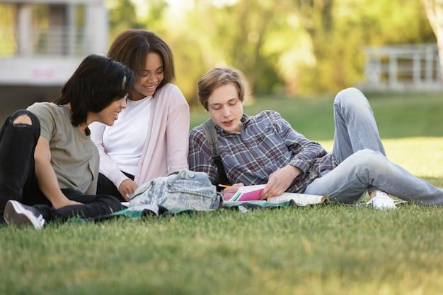Groupe gai d'étudiants multiethniques étudiant à l'extérieur.