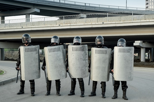Groupe de gardes de police portant des casques tenant des matraques à poignée latérale et des boucliers anti-émeute et se tenant en rang sous les ponts