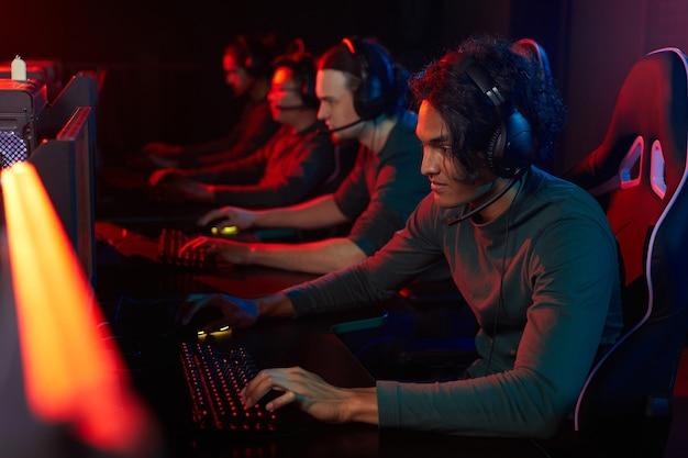 Groupe de gars dans des écouteurs assis à la table devant des ordinateurs et jouer à des jeux informatiques en club informatique