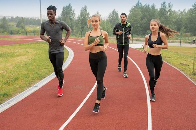 Groupe de gars et de filles actifs en tenue de sport sur les pistes de course sur le stade tout en se préparant pour le marathon