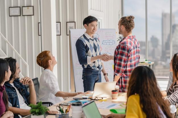 Groupe de gens d'affaires asiatiques et multiethniques avec costume décontracté accueillir un nouveau membre