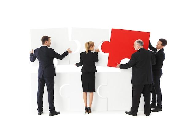 Groupe de gens d'affaires assemblage jigsaw puzzle isolé sur fond blanc