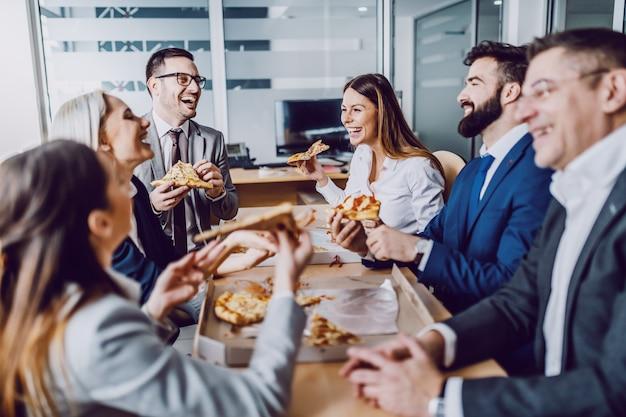 Groupe de gens d'affaires assis dans la salle de conférence, bavardant, riant et prenant une pizza pour le déjeuner.