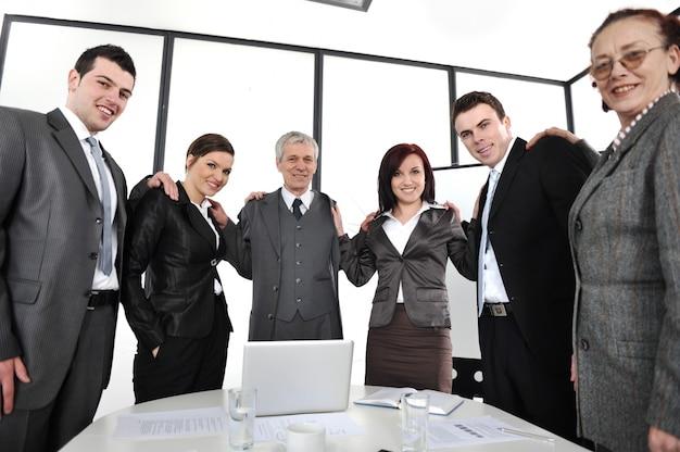 Groupe de gens d'affaires debout au bureau et se tenant les uns les autres