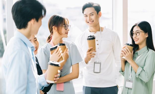 Groupe de gens d'affaires discutent et boivent du café pendant la récréation