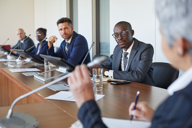 Groupe de gens d'affaires à l'écoute de l'orateur lors d'une réunion d'affaires au bureau