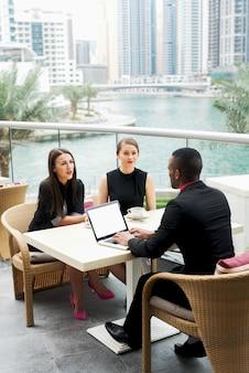 Groupe de gens d'affaires élégants et confiants ayant une conversation dans une belle ville.