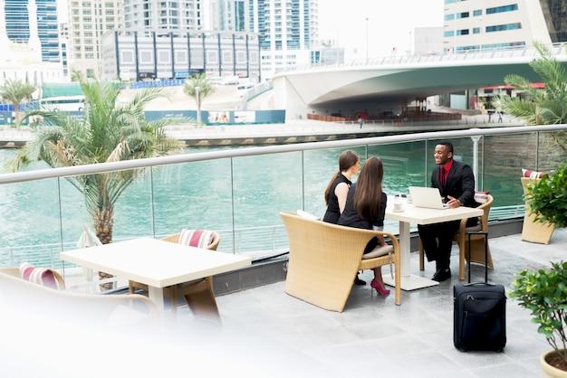 Groupe de gens d'affaires élégants positifs ayant une conversation à la terrasse du café.
