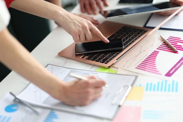 Groupe de gens d'affaires étudiant des graphiques dans des documents et sur des gadgets