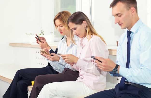 Un groupe de gens d'affaires examinent leur smartphone lorsqu'ils sont assis au bureau.