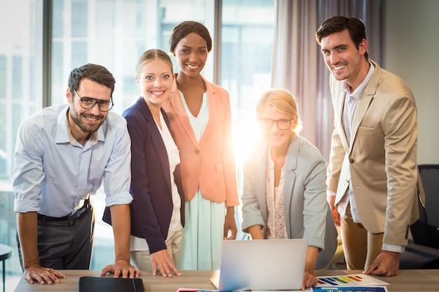 Groupe de gens d'affaires interagissant à l'aide d'un ordinateur portable