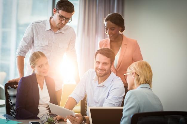 Groupe de gens d'affaires interagissant à l'aide de tablette numérique