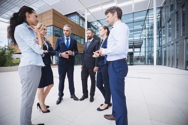 Groupe de gens d'affaires interagissant à l'extérieur de l'immeuble de bureaux