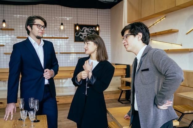 Groupe de gens d'affaires lors d'une réunion debout regroupés dans un bureau