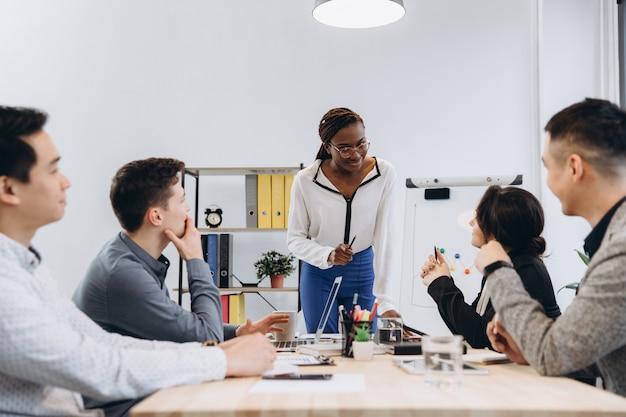 Groupe de gens d'affaires multiculturels écoutant leur discours de patron, femme afro-américaine manager parler à son équipe