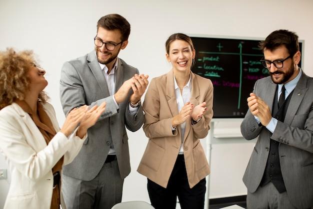 Groupe de gens d'affaires multiethniques applaudissant après une réunion réussie au bureau