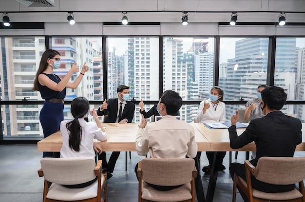 Groupe de gens d'affaires multiethniques portant un masque facial montrant les pouces vers le haut et d'accord d'un accord commercial lors de la réunion dans un nouveau bureau normal
