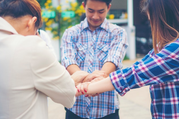 Groupe de gens d'affaires ont croisé les bras dans une pile pour gagner. pile de mains. concept de coopération