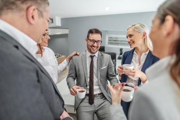 Groupe de gens d'affaires prenant une pause-café au travail et bavarder.