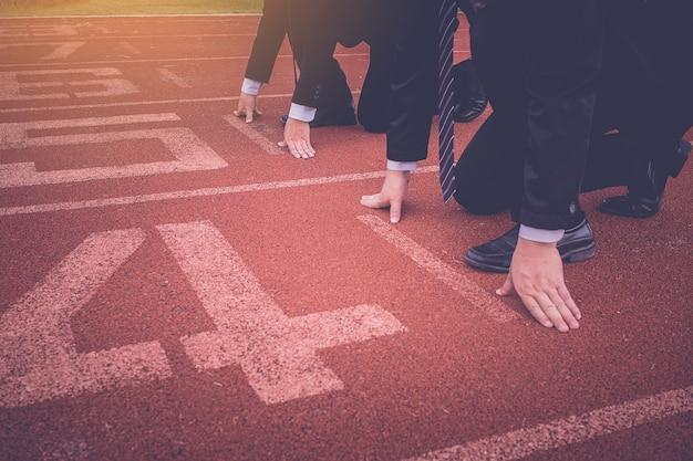 Groupe de gens d'affaires prêts à commencer la course sur piste