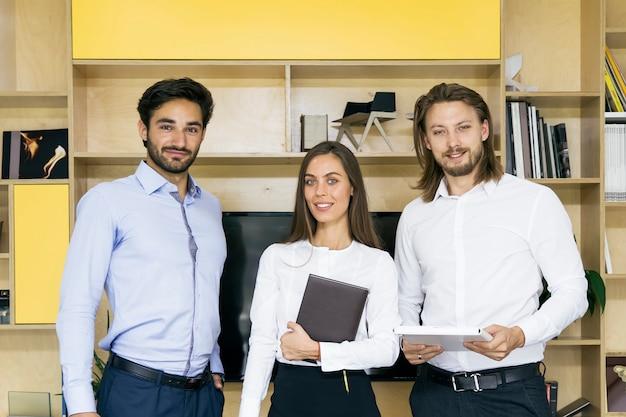 Groupe de gens d'affaires prospères debout ensemble au bureau