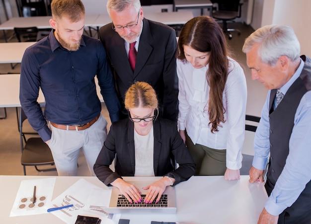 Groupe de gens d'affaires à la recherche à la femme à l'aide d'un ordinateur portable au lieu de travail