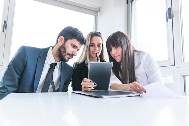 Groupe de gens d'affaires à la recherche d'une tablette numérique au bureau