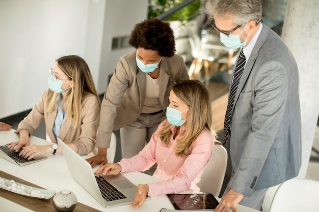 Un groupe de gens d'affaires a une réunion et travaille au bureau et porte des masques comme protection contre le virus corona